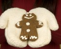 Close up of woman in mittens holding gingerbread man